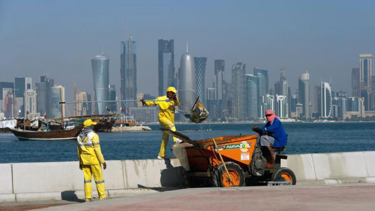 Arbeiter fischen in Doha Müll aus dem Meer. Foto: picture-alliance/ dpa