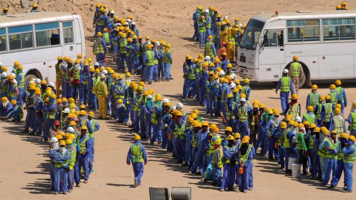 Gastarbeiter warten in der Schlange auf ihren Bus. Foto: picture-alliance/ dpa