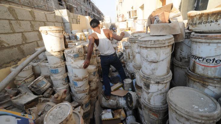 Gastarbeiter inmitten alter Farbeimer. Foto: picture-alliance/ dpa