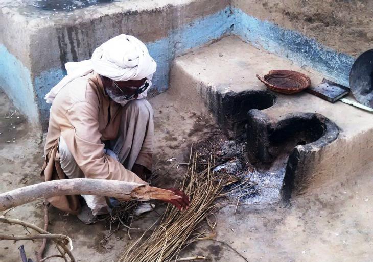 Ein älterer Mann zündet das Feuer an. Foto: Usman Mahar