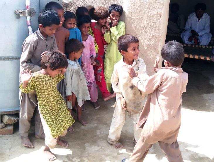 Kinder stehen nebeneinander, während zwei Jungen vor ihnen miteinander kämpfen. Foto: Usman Mahar