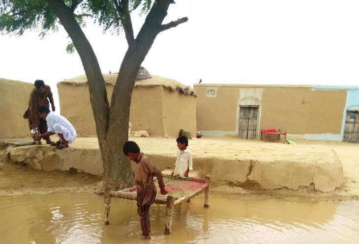 Kinder spielen in einer großen Wasserpfütze. Foto: Usman Mahar