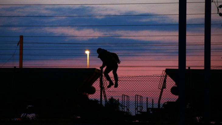 Ein Flüchtling klettert über einen Zaun in der Nähe der Eisenbahnschienen am Eurotunnel. Foto: picture-alliance/ empics/ Y. Mok