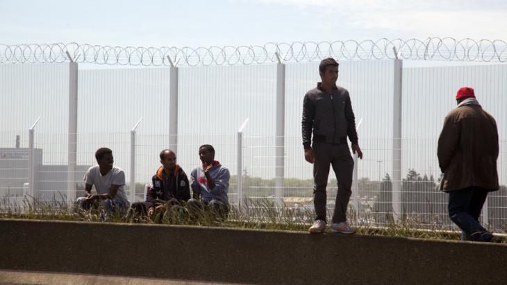 Flüchtlinge lehnen am Grenzzaun in der französischen Hafenstadt Calais. Foto: DW/ L. Scholtyssek