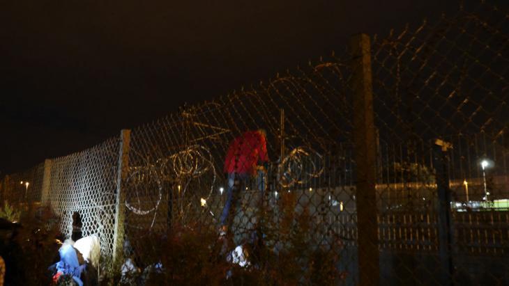Ein Flüchtling übersteigt einen Sicherheitszaun am Eurotunnel in Calais. Foto: DW/ B. Riegert