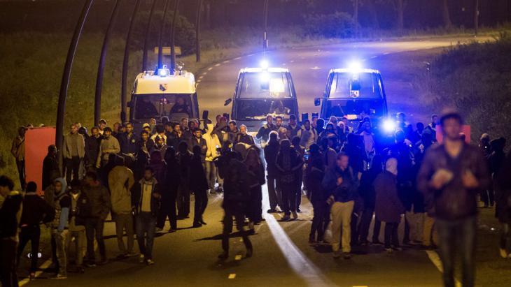 Polizeiwagen eskortieren Migranten vom Eingang des Eurotunnels in der Nähe von Calais. Foto: Getty Images/ AFP/ P. Huguen