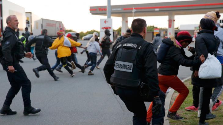 Französische Polizisten jagen Migranten von einer geschlossenen Tankstelle, die als Versammlungsort für die Flüchtlinge gilt, um über den Kanaltunnel nach England zu gelangen. Foto: Reuters/ P. Rossignol