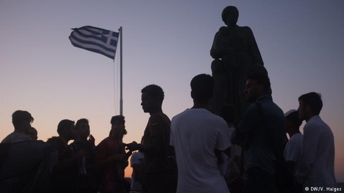 Flüchtlinge vor griechischer Fahne auf Lesbos; Foto: DW/Vincent Haiges