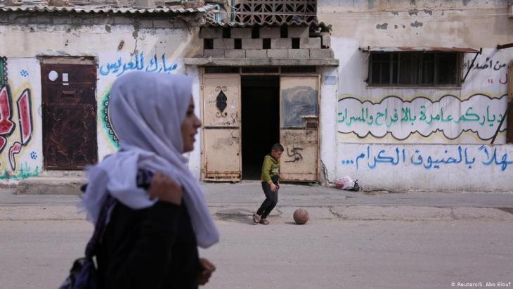 Wessal Abu Amra geht auf ihrem Nachhause-Weg von der Schule an einem spielenden Jungen vorbei; Foto: Reuters/Samar Abo Elouf