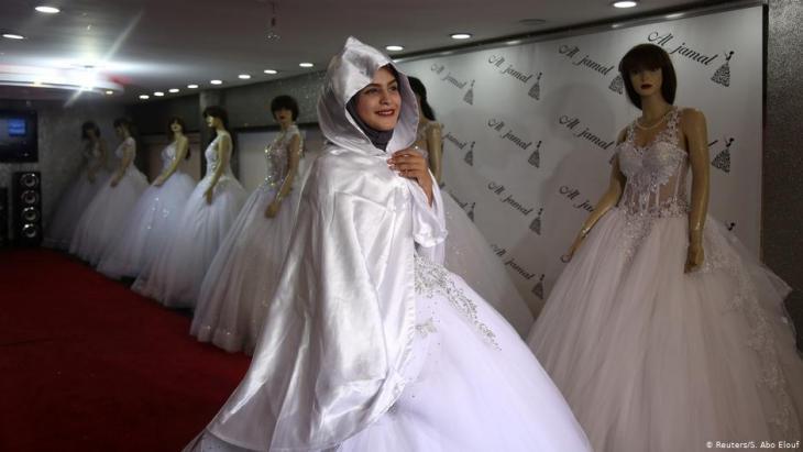 Die Gymnasiastin Hana Abu El-Roos probiert am 26. November 2018 in einem Geschäft in Gaza City ein Hochzeitskleid an; Foto: Reuters/Samar Abo Elouf