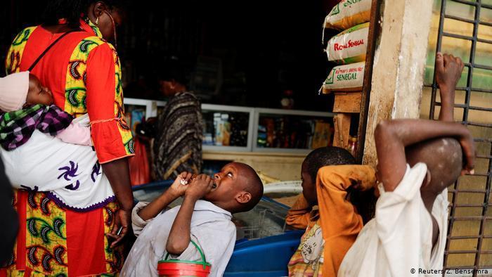 Ein Kind bettelt bei einer Passantin im Senegal; Foto: Reuters