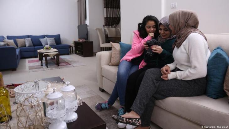 Die 27jährige Nada Rudwan (m.), Absolventin der Englischen Fakultät, schaut Videos von ihr, die von ihrer 22jährigen Schwester Lama Rudwan (r.), beim Kochen in ihrem Haus in Gaza City aufgenommen wurden; Foto: Reuters/Samar Abo Elouf