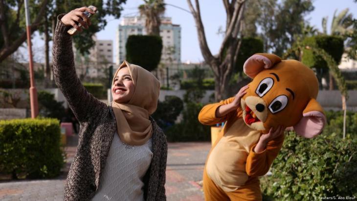 Wessal macht ein Selfie von sich und einer kostümierten Person in einem öffentlichen Park in Gaza City; Foto: Reuters/Samar Abo Elouf