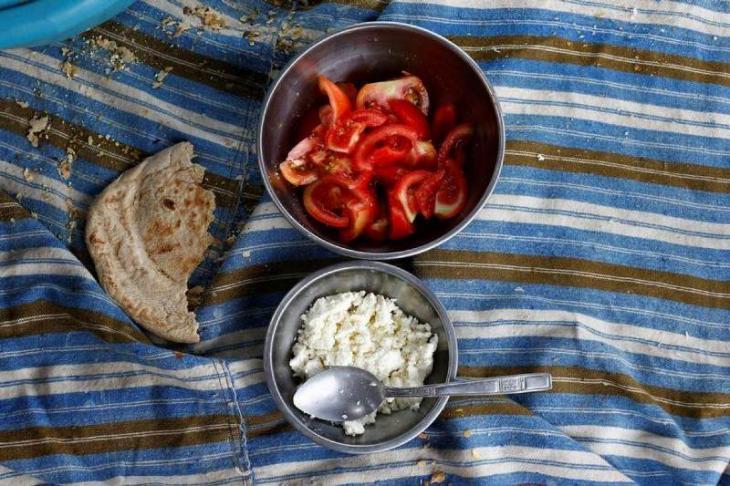 Fladenbrot, Tomaten und Ziegenkäse auf einer Nomadendecke; Foto: Reuters/Osman Orsal