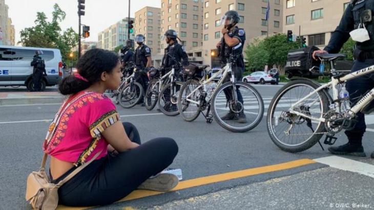 Demonstrantin Deborah sitzt in DC vor einer Reihe Polizisten (DW/C. Bleiker.)