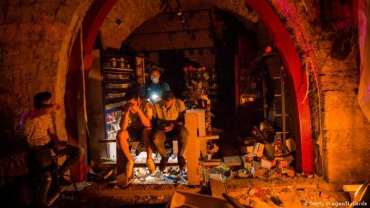 Ein paar Männer sitzen im Halbdunkel vor einem zerstörten Laden, einer checkt sein Telefon (Getty Images/D. Carde)