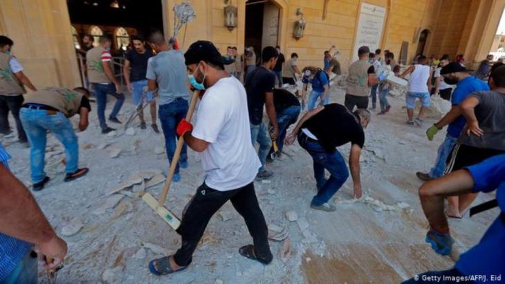 20 bis 30 Personen fegen Staub und Trümmerteile zusammen (Getty Images/AFP/J. Eid)