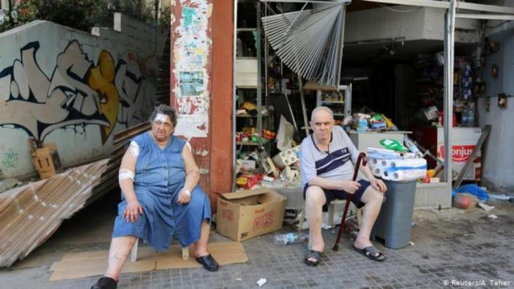 Ein älterer Mann und eine ältere Frau, sie mit Binden und Pflastern, sitzen vor ihrem zerstörten Lebensmittelgeschäft Reuters/A. Taher)