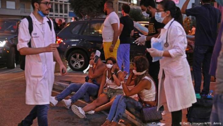 Menschen sitzen vor einem Krankenhaus auf dem Boden, medizinisches Personal geht an ihnen vorbei (Getty Images/AFP/I. Amro)