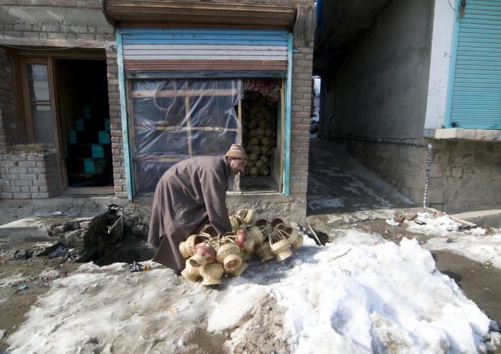 Ein Kangdi-Verkäufer mit seiner Ware in einer verschneiten Nebenstraße von Srinagar. Foto: Sugato Mukherjee