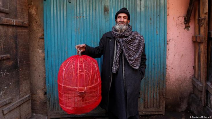 Fatih, 70, hält einen Käfig mit Rebhühnern in der Hand, während er für ein Bild auf dem Vogelmarkt Ka Faroshi in Kabul, Afghanistan, posiert. Foto: REUTERS/Mohammad Ismail