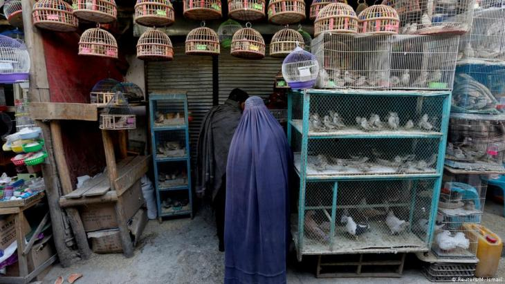 Eine Afghanin in Burka steht vor einem Laden auf dem Vogelmarkt Ka Faroshi in Kabul, Afghanistan. Foto: REUTERS/Mohammad Ismail