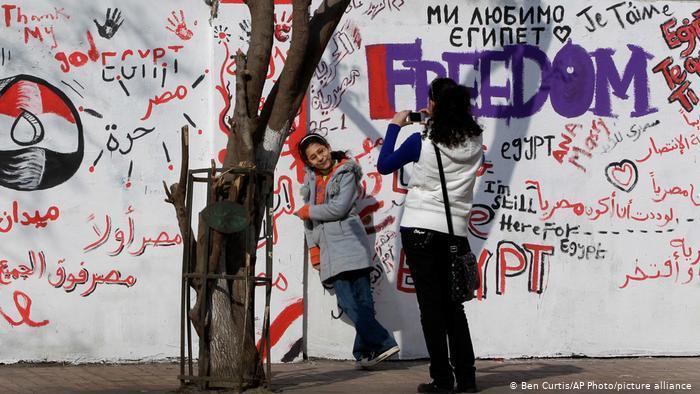Eine junge Frau nimmt ein Foto vor einem Graffiti in Kairo auf. Foto: picture-alliance/AP Photo/Ben Curtis