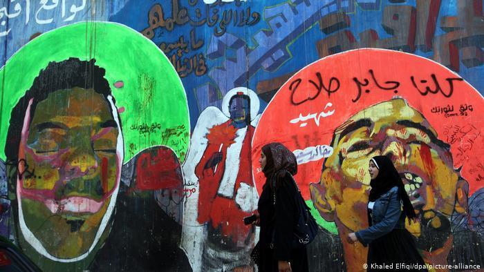 Ein Graffiti zeigt den Blogger Khaled Said mit geschlossenen Augen. Daneben ist eine Frau gemalt die eine rote Rose in der Hand hält. Foto: picture-alliance/dpa/Khaled Elfiqi