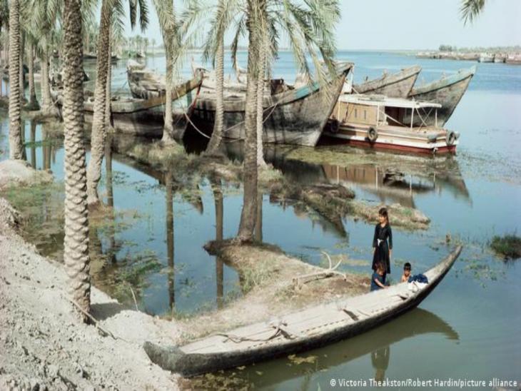 Holzboote liegen am palmenbewachsenen Ufer des Tigris; zwei Kinder stehen im Wasser neben einem Kanu; Foto: Viktoria Theakston/Robert Hardin/picture alliance