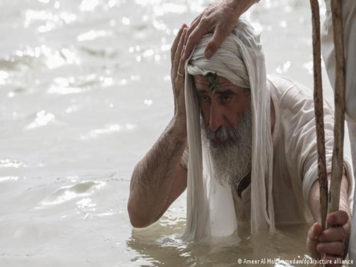 Ein alter Mann im weißen Gewand kniet im Fluss, jemand hat eine Hand auf seinen Kopf gelegt; Foto: Ameer alMohammedaw/dpa/picture alliance