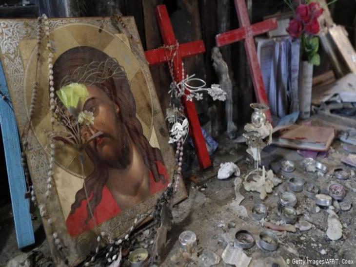 Zerstörte Gegenstände in einem Kirchenraum: Ein Jesusbild udn kerzeln liegen auf dem Boden; Foto: Getty Images/AFP/T. Coex