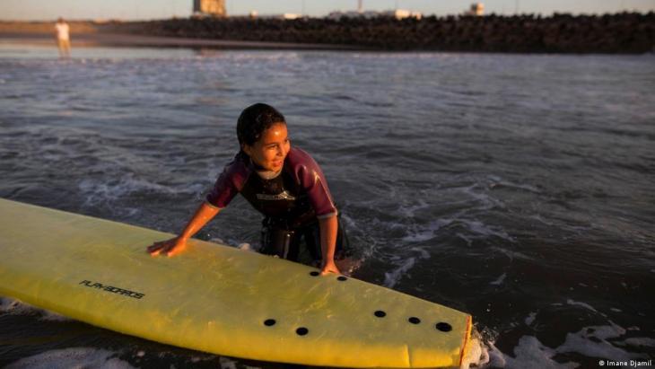 Eine Schülerin hält sich während einer kostenlosen Surfstunde an einem Surfbrett fest. Foto: Imane Djamil