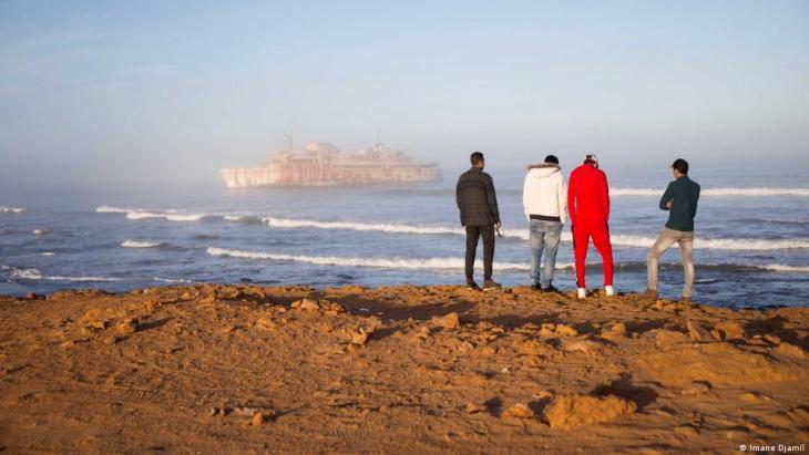 Hassan Boulahcen, 27, ein Surftrainer, Maatoug, Hossin Ofan, 34, der allgemeine Koordinator des Surfclubs Nuevas Olas, und Oussama Segari, 26, der als Schatzmeister des Clubs und Manager des Coffeeshops arbeitet, blicken vor dem Armas-Schiffswrack auf das Meer. Foto: Imane Djamil