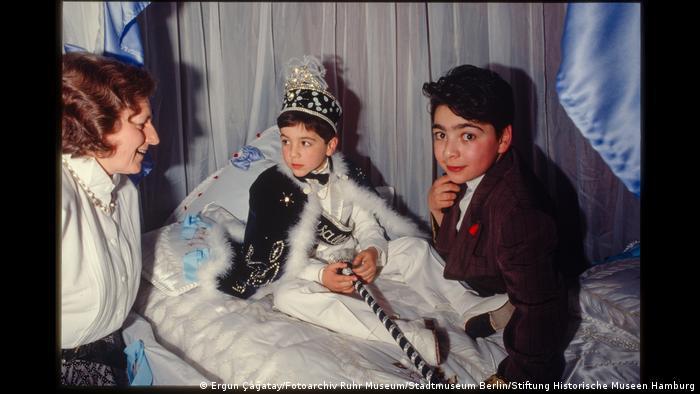 """Junge bei seinem Beschneidungsfest in festlicher Kleidung, neben ihm ein anderer Junge und eine Frau. Aus der Ausstellung """"Wir sind von hier. Deutsch-Türkisches Leben 1990""""."""