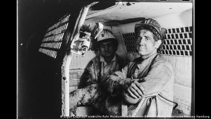 """Zwei Bergleute in einem Personenwagen im Bergwerk Walsum, Duisburg. Aus der Ausstellung """"Wir sind von hier. Deutsch-Türkisches Leben 1990""""."""