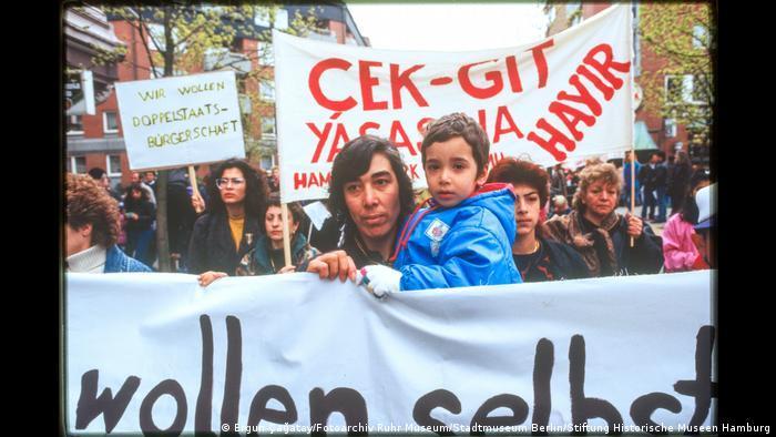 """Demonstrierende mit Bannern. Aus der Ausstellung """"Wir sind von hier. Deutsch-Türkisches Leben 1990""""."""