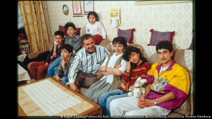 """Eine achtköpfige Familie sitzt auf einem Sofa. Aus der Ausstellung """"Wir sind von hier. Deutsch-Türkisches Leben 1990""""."""