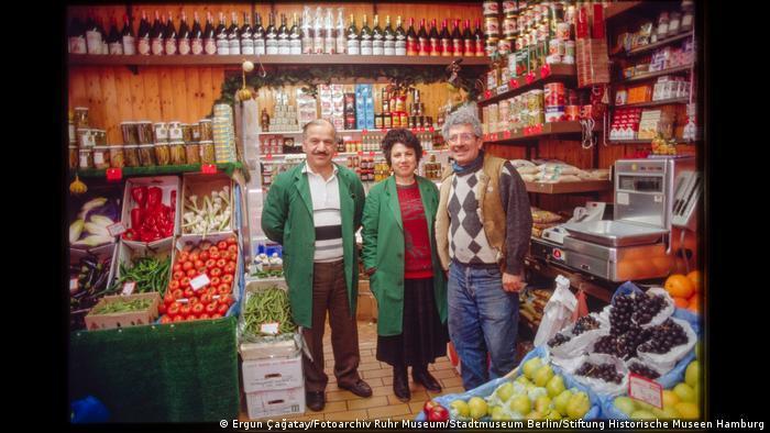 """Drei Menschen stehen in einem Lebensmittelladen und lächeln in die Kamera. Aus der Ausstellung """"Wir sind von hier. Deutsch-Türkisches Leben 1990""""."""