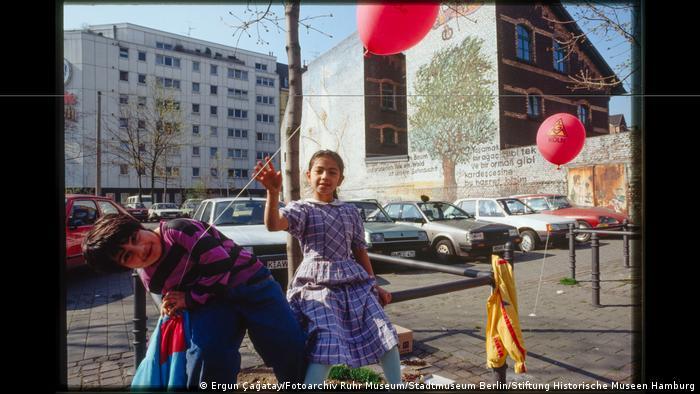 """Zwei Kinder mit Luftballons vor einem Parkplatz. Aus der Ausstellung """"Wir sind von hier. Deutsch-Türkisches Leben 1990""""."""