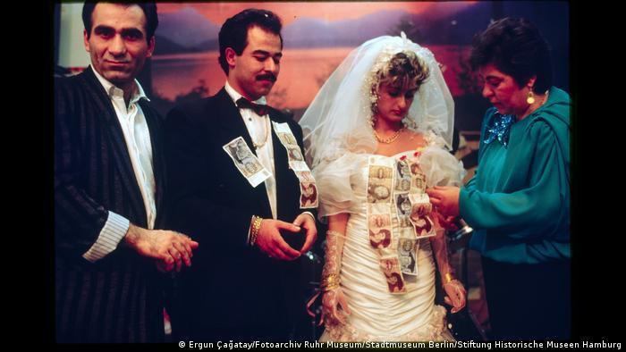 """Hochzeitspaar bekommt Geldscheine angeheftet. Aus der Ausstellung """"Wir sind von hier. Deutsch-Türkisches Leben 1990""""."""