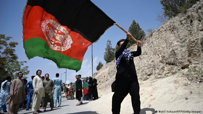 Afghane schwenkt eine große afghanische Landesfahne