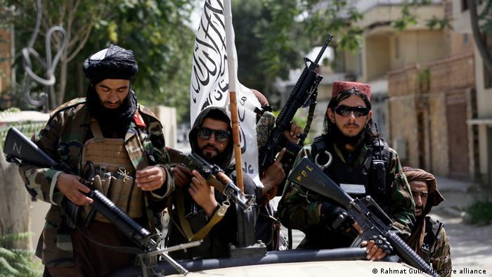 Taliban-Kämpfer mit Waffen und ihrer Flagge in Kabul