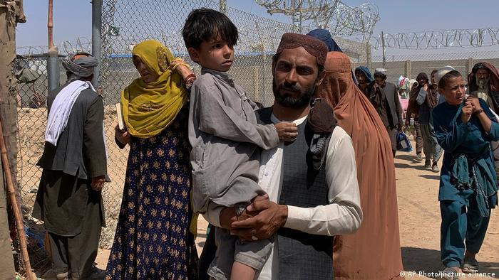 Ein Mann trägt einen kleinen Jungen am Grenzübergang Spin Boldak/Chaman