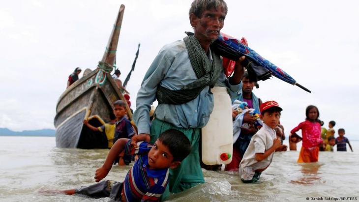 Ein Rohingya-Flüchtling zieht ein Kind mit sich, während sie in Richtung Küste laufen, nachdem sie die Grenze zwischen Myanmar und Bangladesch am Golf am 10. September 2017 mit dem Boot in Shar Powrir Dip im Golf von Bengalen überquert haben; Foto: REUTERS/Danish Siddiqui