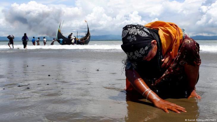 Eine erschöpfte Rohingya-Frau berührt den Boden der Küste, nachdem sie die Grenze zwischen Myanmar und Bangladesch am Golf am 11. September 2017 mit dem Boot in Shar Powrir Dip im Golf von Bengalen überquert hat; Foto: REUTERS/Danish Siddiqui