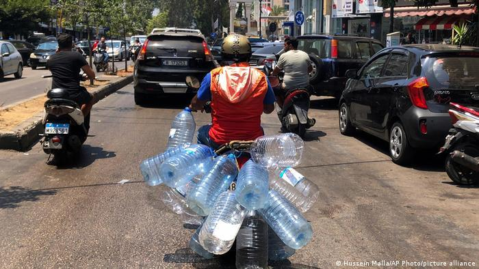 Mofa-Fahrer transportiert leere Wasserflaschen aus Plastik in Beirut.