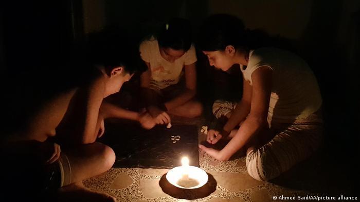 Kinder spielen beim Kerzenlicht.