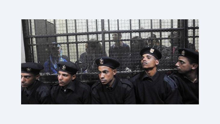 Einheimische Stiftungsmitarbeiter werden im Gerichtssaal in Kairo in einem Käfig vorgeführt; Foto: EPA