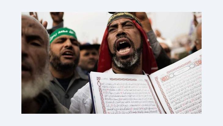 Anhänger Mohammed Mursis hält während einer Demonstration in Kairo den Koran hoch; Foto: AFP/Getty Images
