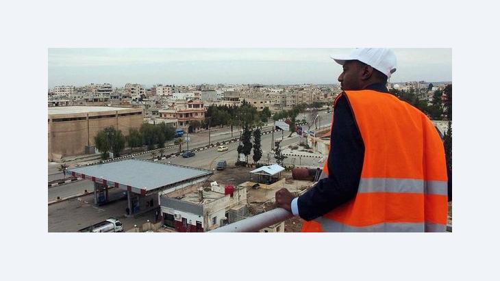 Ein Beobachter der Arabischen Liga überblickt von einer Terrasse die südsyrische Stadt Daraa, eine Hochburg der Proteste; Foto: dpa